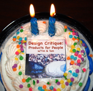 Photo of birthday cake w/2 candles burning on it and a Design Critique album art on top of the frosting.