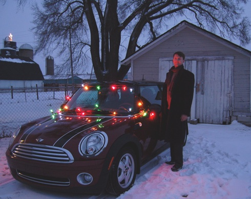 Photo of Tim in front of MINI Cooper with Christmas lights glowing on it.